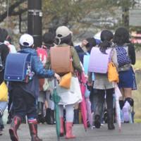 クマよけの鈴をランドセルにさげて集団下校する小学生ら=小松市内で、深尾昭寛撮影