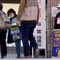 投票所前で、訪れた有権者に「反対」を訴える人たち=大阪市都島区で2020年11月1日午前9時56分、平川義之撮影
