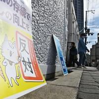 投票所前に置かれた、有権者に反対を訴えるポスター=大阪市北区で2020年11月1日午後0時34分、山崎一輝撮影