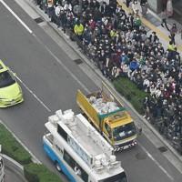 街頭演説の準備をする大阪維新の会の車両(手前)の前を通過する自民党の車両(中央)=大阪市中央区で2020年11月1日午前11時51分、本社ヘリから大西達也撮影