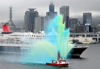 Cruise ship the Nippon Maru is seen departing from the Port of Kobe while a city government fireboat shoots colored water into the sky to celebrate, on Nov. 2, 2020. (Mainichi/Naohiro Yamada)