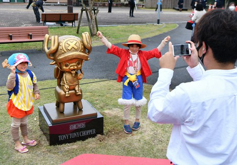 "Two sisters dressed up as ""One Piece"" protagonist Luffy, right, and Chopper, left, are seen posing for a photo with the statue of Chopper at the Kumamoto City Zoological and Botanical Gardens in the city's Higashi Ward on Nov. 7, 2020. (Mainichi/Kohei Shimizu)"