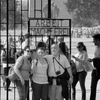 ドイツのザクセンハウゼン強制収容所の玄関、「働けば自由になる」という標語の前で記念撮影する観光客=映画「アウステルリッツ」よりⒸSunny-film