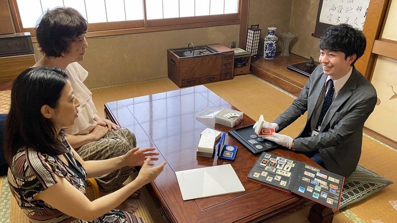 個人宅を訪問し、切手やコインを査定するバイセルテクノロジーズのスタッフ(右)=東京都内で同社提供