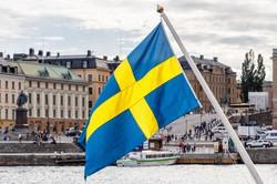 スウェーデンの国旗と首都ストックホルムの風景(ゲッティ)