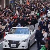 紙吹雪が舞う中を優勝パレードする琴奨菊(車上右)と佐渡ケ嶽親方=千葉県松戸市で2016年2月21日、橋口正撮影