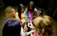 Catherine Gallano, dancer and lead choreographer, 1st left, prays with her group before they start their livestream performance on social media for followers who send them money, in Dubai, United Arab Emirates, on Nov. 5, 2020. (AP Photo/Kamran Jebreili)