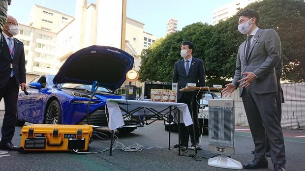 トヨタの新型FCV「ミライ」の燃料電池で証明器具やストーブをつけ、「動く蓄電池」としての機能を確認する小泉環境相(右端)=環境省で2020年11月10日午後0時21分、鈴木理之撮影