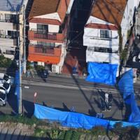 発砲事件のあった建物を調べる捜査員ら=兵庫県尼崎市で2020年11月18日午前9時半、本社ヘリから
