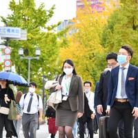 夏日となり、イチョウ並木の御堂筋を日傘を差すなどして歩く人たち=大阪市北区で2020年11月19日午後2時33分、北村隆夫撮影