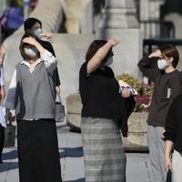 強い日差しを手で遮り信号待ちをする人たち=大阪市北区で2020年11月19日午後0時55分、北村隆夫撮影