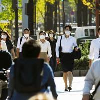 季節外れの夏日となり、イチョウ並木の御堂筋を上着を脱いだり、シャツを腕まくりしたりして歩く人たち=大阪市で2020年11月19日午後1時7分、北村隆夫撮影