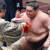 御嶽海を寄り切りで破り、懸賞金を受け取る照ノ富士=東京・両国国技館で2020年11月19日、宮武祐希撮影