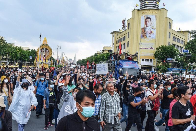 「反独裁」を意味する3本指を立て、デモを続けるタイの若者たち