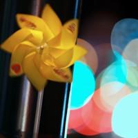 「世界道路交通犠牲者の日」に合わせて、県警が死亡事故現場に設置した黄色い風車。背後には行き交う車や信号の灯りが浮かぶ=秋田市で2020年11月11日、小川昌宏撮影