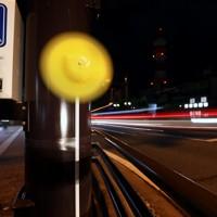 「世界道路交通犠牲者の日」に合わせて、県警が死亡事故現場に設置した黄色い風車。行き交う車のライトが光の筋を残す=秋田市で2020年11月11日、小川昌宏撮影