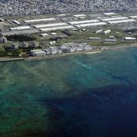 サンゴ礁に囲まれたイノーが続く浦添市の西海岸。写真の右側の海域が埋め立てられる予定になっている。海岸に近い白く細長い屋根はキャンプ・キンザーの倉庫群=沖縄県浦添市で2020年10月、本社機「希望」から撮影