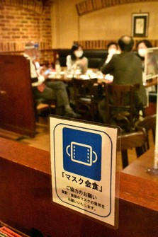 A sticker that calls for customers to dine while wearing their masks is seen at the Shinjuku establishment of beer hall chain Ginza Lion in Tokyo on Nov. 20, 2020. (Mainichi/Nobuyuki Shimada)