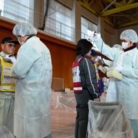 原子力災害訓練で、放射性物質が付着していないかを調べるスクリーニング検査を行う参加者たち=青森市で2013年11月23日午前11時12分、伊藤奈々恵撮影