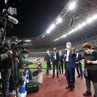 国立競技場を視察し、記者団の質問に答えるIOCのバッハ会長(右中央)=東京都新宿区で2020年11月17日(代表撮影)