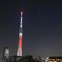 東京スカイツリーのそばを東に向かって飛行する、国際宇宙ステーション(ISS)の光跡。右下は月(午後6時19分から2秒間隔で撮影した38枚の写真を比較明合成)=東京都墨田区で2020年11月18日午後6時19分、手塚耕一郎撮影