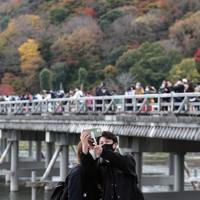 3連休の初日、紅葉の見ごろを迎えた京都の嵐山を訪れた観光客=京都市右京区で2020年11月21日午前、小出洋平撮影