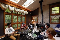 People who have moved to the Nagano Prefecture town of Karuizawa enjoy a discussion in a holiday home in the town, in a room heated with a wood-burning stove, with skylights allowing light in, on Oct. 21, 2020. (Mainichi/Masahiro Ogawa)