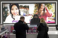 Cashier Druhan Parker, center, works behind a plexiglass shield on Nov. 19, 2020, as he checks out shoppers at an Ulta beauty store on Chicago's Magnificent Mile. (AP Photo/Charles Rex Arbogast)