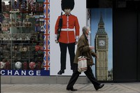 A person wearing a face mask walks past a temporarily closed souvenir store on Oxford Street during England's second coronavirus lockdown, in London, on Nov. 23, 2020. (AP Photo/Matt Dunham)