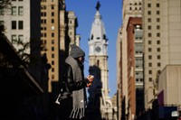In this Nov. 18, 2020 photo, a person wearing a face mask crosses Broad Street in Philadelphia. (AP Photo/Matt Slocum)