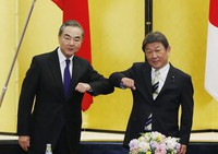 China' Foreign Minister Wang Yi, left, and his Japanese counterpart Toshimitsu Motegi bump elbows at the start of their talks amid the coronavirus outbreak, in Tokyo on Nov. 24, 2020. (Issei Kato/Pool Photo via AP)