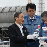 汚染処理水の入った瓶を手に東京電力の説明を受ける菅義偉首相(左端)=東電福島第1原発で2020年9月26日(代表撮影)