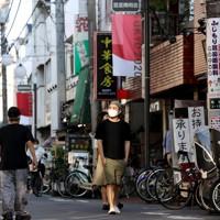 自宅近くの商店街を歩くマレーシアから来たロエクス・タンさん(中央)。東京五輪開催も楽しみにしていたので、延期は残念だったと話す=東京都中野区で2020年9月21日、宮武祐希撮影