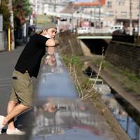 自宅近くの散歩コースの途中にある川を眺めるマレーシアから来たロエクス・タンさん(右)。新型コロナウイルスの影響もありアルバイトも無く、母国で貯めたお金を切り崩しながら生活する。自宅で日本語の勉強をするか、自宅近くを散歩するのが日課だという=東京都中野区で2020年9月21日、宮武祐希撮影