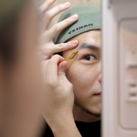 自宅で身だしなみを整えるマレーシアから来たロエクス・タンさん。母国では俳優として仕事をしていた。見た目には特に注意をしているという=東京都中野区で2020年9月21日、宮武祐希撮影