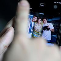 スマートフォンで、ロエクスさんがマレーシアで出演した番組出演者たちと撮影した記念写真を見せてくれた=東京都中野区で2020年9月21日、宮武祐希撮影