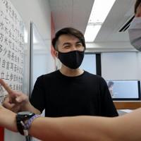 語学学校の教室で台湾からの留学生(右)と日本語を教え合うタンさん=東京都新宿区で2020年9月9日、宮武祐希撮影