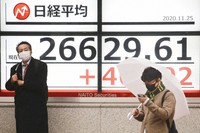 People stand by an electronic stock board of a securities firm showing Japan's Nikkei 225 index in Tokyo, on Nov. 25, 2020. (AP Photo/Koji Sasahara)