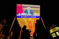In this Nov. 22, 2020 file photo, people gather near a giant TV screen broadcasting a news of Chinese President Xi Jinping speaks as he participates in a virtual G20 summit, at a shopping mall in Beijing. (AP Photo/Andy Wong)