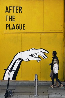 Pedestrians walk past a COVID-19-themed mural outside a boarded-up business on Nov. 23, 2020, in Santa Monica, California. (AP Photo/Marcio Jose Sanchez)