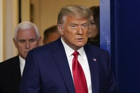 U.S. President Donald Trump, followed by Vice President Mike Pence, left, walks into the briefing room at the White House in Washington on Nov. 24, 2020. (AP Photo/Susan Walsh)