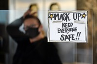 In this Nov. 17, 2020 file photo, manager Yllka Murati waits for a delivery driver to pick up takeout orders behind a partition displaying a sign to remind customers to wear a mask, at the Penrose Diner, in south Philadelphia. (AP Photo/Matt Slocum)