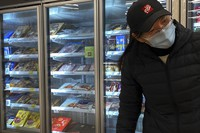 A woman wearing a face mask walks by a fridge displaying frozen meats at a supermarket in Beijing, on Nov. 24, 2020. (AP Photo/Andy Wong)
