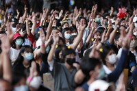 A crowd flashes the three-finger protest gesture during a student rally in Bangkok on Nov. 21, 2020. (AP Photo/Sakchai Lalit)
