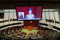 A TV screen shows Hong Kong Chief Executive Carrie Lam delivering her policies at chamber of the Legislative Council in Hong Kong, on Nov. 25, 2020. (AP Photo/Kin Cheung)