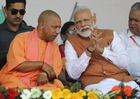 In this March 28, 2019, file photo, Indian Prime Minister Narendra Modi, right, speaks with Chief Minister of Uttar Pradesh state Yogi Adityanath during an election campaign rally in Meerut, India. (AP Photo/Altaf Qadri)