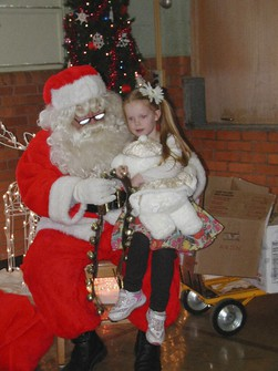 In this Dec. 15, 2012, photo provided by Carolyn Plotts, Evelyn Spanier, 4, visits Santa following the annual Norcatur Christmas Drawing in Norcatur, Kan. (Courtesy of Carolyn Plotts via AP)