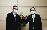 Japan's Prime Minister Yoshihide Suga, right, bumps fists with China's Foreign Minister Wang Yi at the start of their meeting in Tokyo, on Nov. 25, 2020. (Behrouz Mehri/Pool Photo via AP)