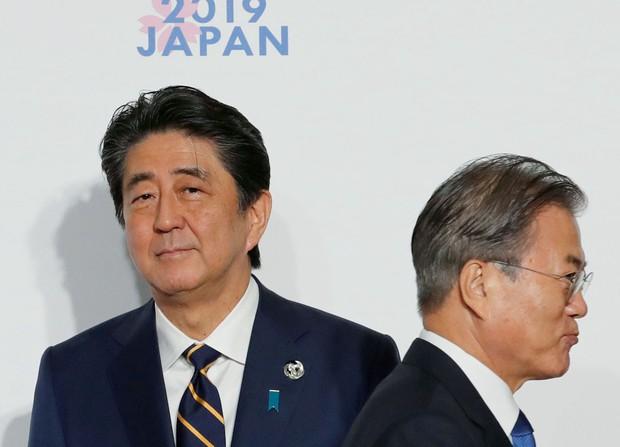 元徴用工問題で手続き進む 信頼崩壊、非難合戦に  2019年6月、G20大阪サミットで握手した後、すれ違う韓国の文在寅大統領(右)と安倍首相=大阪市(ロイター=共同)