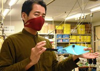 Kosuke Inoue is seen wearing a mask that can stay on without being attached to the ears while showing another one. (Mainichi/Atsuki Nakayama)